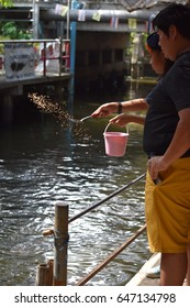 Sower's hand with fish food throwing to water at the Klong Lad Ma Yom  floating market in Bangkok  Thailand on May 21th,2017;Editorial use only
