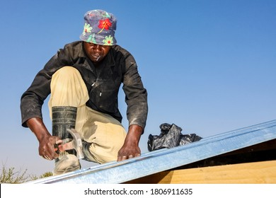 Soweto, South Africa - September 05, 2009: Community Outreach program helping to install metal roofing on a small affordable house in local township