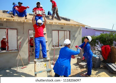 Soweto, South Africa, September 10, 2011,  Diverse Community members building a low cost house as a team in Soweto