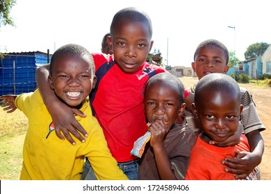Soweto, South Africa - September 7, 2011: Small group of young African children posing for a photo and displaying friendship and joy in a Soweto Township