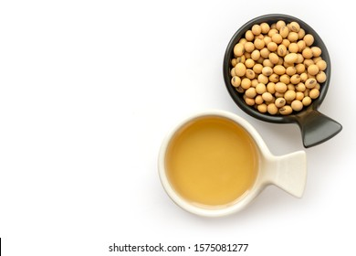Soy bean oil with soybean seeds in ceramics bowl isolated on white background. Top view. Flat lay. Space for text.