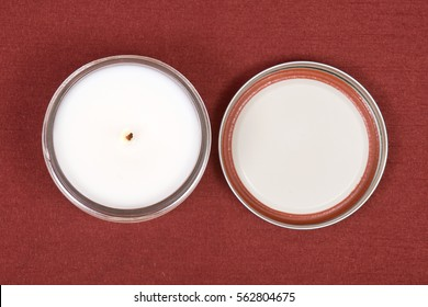 Soy candle in glass jar on red fabric background