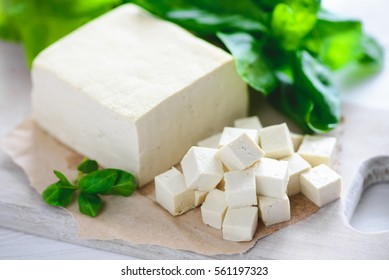 soy cheese tofu diced on a cutting board, basil closeup