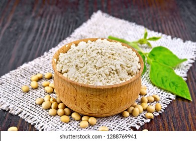 Soy flour in the bowl, soybeans on burlap, green leaf on a wooden board background
