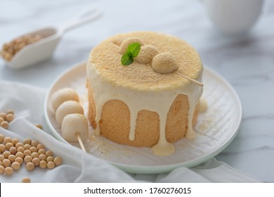 Soy milk cake with glutinous rice balls and soybean based cream dripping on the cake. Soybean meal dusted on the cake,background is some soybean and cup