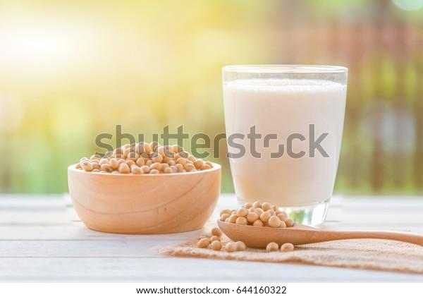 玻璃豆漿和豆漿勺子它在白桌背景上,早晨照明,健康的概念。