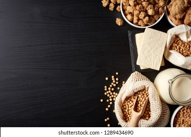 Soy products: soy beans, soy milk, tofu and soya chunks on black background, top view; copy space