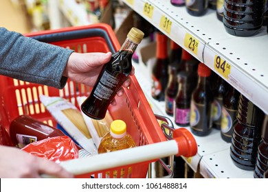 Soy sauce bottle in the hand of the buyer at the grocery store