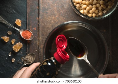 Soy sauce is poured into a spoon over the saucepan