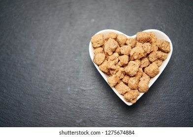 Soya protein chunks in a heart shape. I love soy chunks. Vegan food concept. Healthy, nutritious soybean meat, chunks in a bowl. Copy space, place for text.