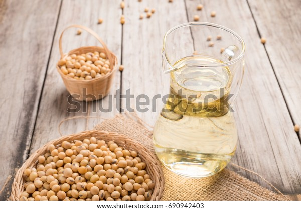Soybean in basket and soybean oil in jar on wooden background