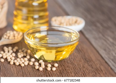 Soybean oil and Soybean on wooden table.