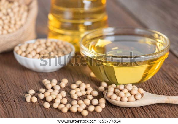 Soybean oil and Soya on wooden table.