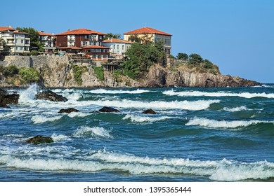 Sozopol, Bulgaria. East cape of Sozopol Old Town (former ancient town of Apollonia) with yellow building of Art Gallery. View from the city's central beach across the bay with storm waves.