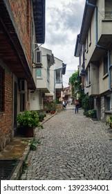 Sozopol, Bulgaria - September 06, 2014: Narrow street of the old town of Sozopol. Retro houses and cobblestone pavement. Vertical shot.