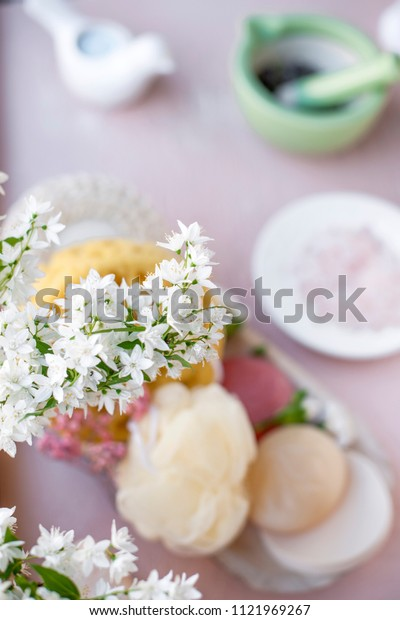 spa accessories and flowers. pink background. Copy space.