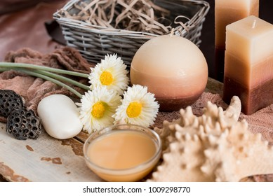 Spa accessories with soap, bowl with dried chamomile flowers, A piece of white soap, liquid brown soap, seashell shell, aromatherapy candles, dried lotus flower seeds. On a wooden background