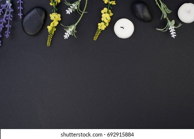 Spa and aromatherapy concept on black background. Zen stones, accessories used in aromatherapy. Flat lay. Top view.