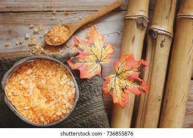 Spa background with bamboo, bath salt in coconut, autumn leaves and towel.