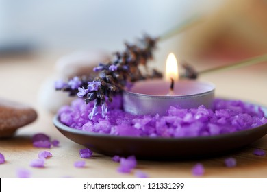 Spa background, candle in a saucer with salt baths and sprigs of lavender