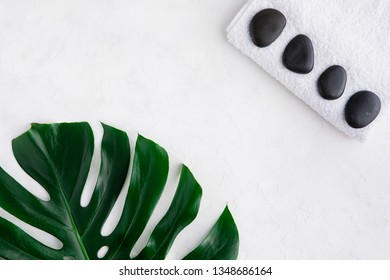 Spa background, palm leaves and black wet stones, top view and flat lay