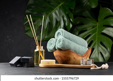 Spa and bath concept. Green tea scrub, coal black soap, eucalyptus, oil, sea stones, towels and body brush on black background with tropical leaves. Copy space.