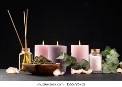 Spa and bath concept. Green tea scrub, eucalyptus, sea salt and candles on black background. Copy space.