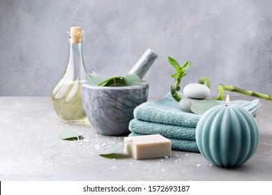 Spa and bath concept. Oil for body massage, sea stones, vanilla soap with coconut for scrub, towels, eucalyptus leaves in a mortar and branch fresh bamboo on light grey background. Copy space
