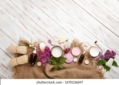 Spa and bath cosmetics with lilac flowers. Bath salt, soap, cream, oil, serum and towel rolls on wooden rustic background. Organic natural cosmetic. Fresh care of body. Banner with copy space top view