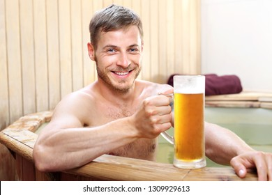 Spa bath. Handsome man enjoys bathing in logs with thermal water drinking beer mug.