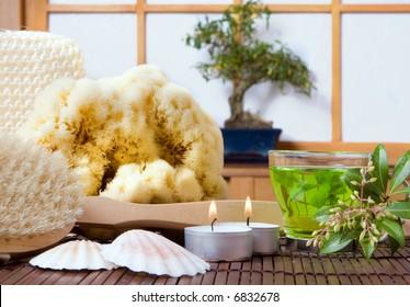 Spa bath products, green tea and bonsai tree against a traditional japanese shoji sliding window