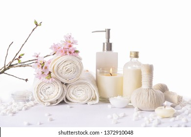 Spa bath setting with cherry flower with salt in spoon in bowl,candle, herbal ball ,bottle oil ,stones, brush,rolled towel