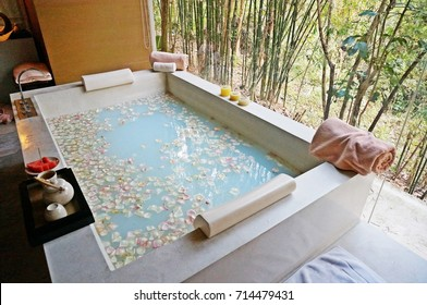 Spa bath tub with lotus petals and milk inside. Around with towels, candles, fruit and tea.