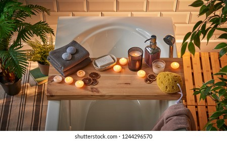 Spa bathtub wooden table vase of plant candle towel brush all kind of spa object. Modern spa center.
