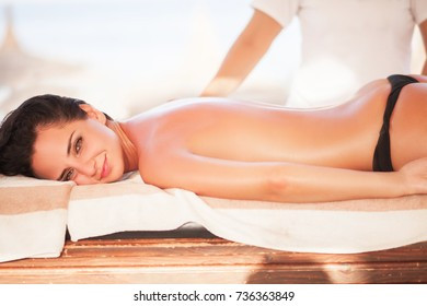 Spa. Beautiful woman get massage on sunny beach. Relax on vacations.