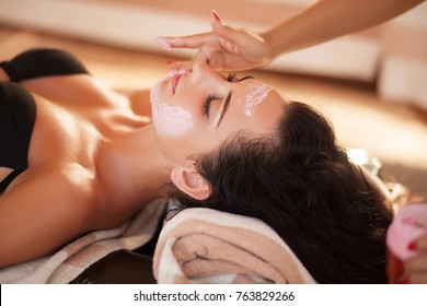 Spa. Beautiful woman relaxing during rejuvenating facial massage in a modern beauty center