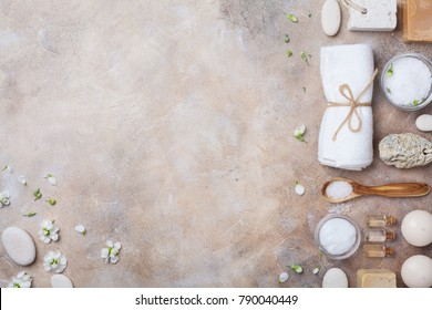 Spa and beauty conceptual stone background from handmade body care and aromatherapy supplies decorated flowers. Top view. Flat lay.