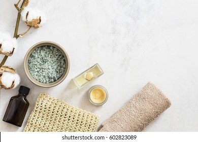 Spa beauty cosmetic products and tools on white marble background from above. Copyspace