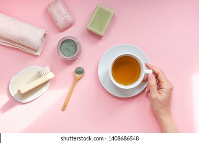 Spa, beauty cosmetics and body care treatment concept copy space. Creative top view flat lay of woman hands with bath accessories, green spirulina cleansing mask in bowl, cup of tea pink background
