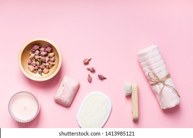 Spa, beauty cosmetics and body care treatment concept with copy space. Creative top view flat lay composition with bath accessories, organic DIY rose soap and dry flowers in a bowl on pink background