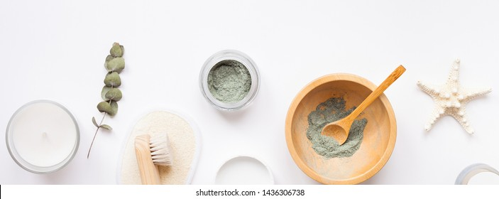 Spa, beauty cosmetics and body care treatment concept with copy space. Creative top view flat lay composition with bath accessories green spirulina cleansing mask in wooden bowl on white background