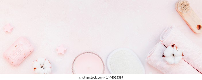 Spa, beauty cosmetics and body care treatment concept with copy space. Creative top view flat lay composition with bath accessories and rose soap cotton flowers, loofah on pink marble table background