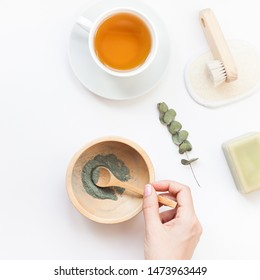 Spa, beauty cosmetics and body care treatment concept with copy space. Creative top view flat lay composition cup of tea, green spirulina cleansing mask in wooden bowl woman hands on white background