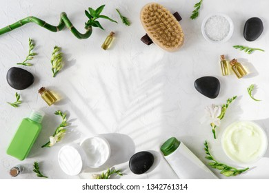Spa beauty cosmetics of bottle, palm leaf, on white marble table with sunlight and shadows, flat lay and top view. Copy space