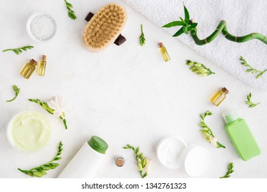 Spa beauty cosmetics of bottle, palm leaf, on white marble table, flat lay and top view. Copy space