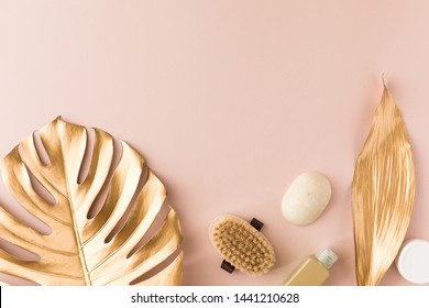 Spa beauty cosmetics on pink table with gold tropical leaves, view from above. Top view, flat lay, Copy space