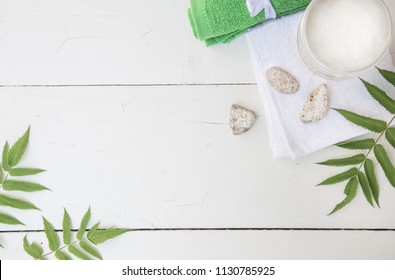 Spa beauty cosmetics on white marble table from above . Copy space. Flat layout. a jar of cream, leaves, flowers and a towel on a wooden background