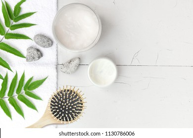 Spa beauty cosmetics on white marble table from above . Copy space. Flatlay. a jar of cream, leaves, flowers and a towel on a wooden background