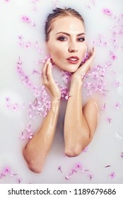 Spa beauty model girl bathing in milk bath, spa and skin care concept. Beauty young Woman with perfect slim body and soft skin, in flower wreath relaxing in milk bath. Rejuvenation