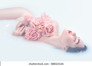 Spa beauty model girl taking milk bath, spa and skin care concept. Beauty young Woman with bright makeup and pink rose flower relaxing in milk bath. Rejuvenation.
